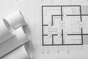 Architect house plan roled -up plans on the table, high angle view.