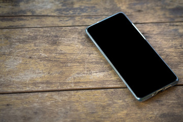Smartphone or mobile phone (unrecognized model or brand) is placed on wooden texture surface. Providing display screen as black background for logo space for business concept.