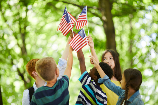 Group of patriotic multi-ethnic children standing in circle and raising us stick flags together