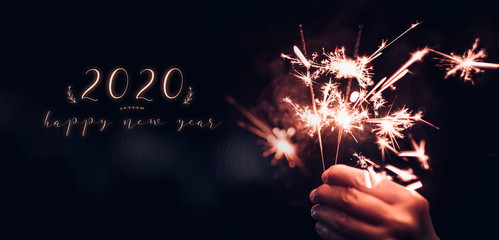 happy new year 2020 text with hand holding burning Sparkler firework blast with on a black bokeh background at night,holiday celebration event party,dark vintage tone.