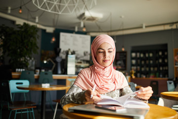 Serious young Muslim woman sitting at cafe table, reading book and taking notes