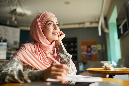 Pretty positive young woman in hijab writing her dreams in diary when sitting at table in cafe