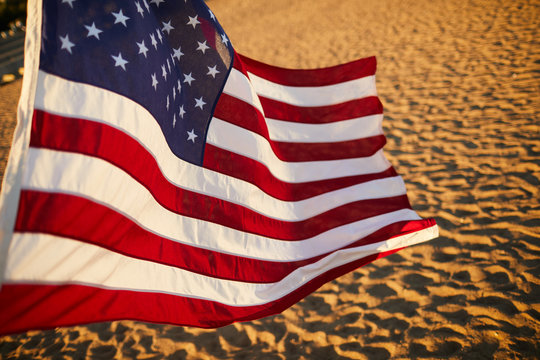 Close-up of American flag with stripes and stars blowing in wind on summer beach at sunset