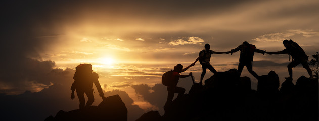 Silhouette of Hikers climbing up mountain cliff. Climbing group helping each other while climbing up in sunset. Concept of help and teamwork, Limits of life and Hiking success full. Wall mural