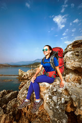 Adventure trek along the coast with a backpack in the summer.