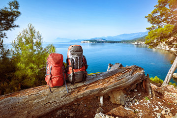 Hike with backpacks along the Mediterranean Sea in summer.