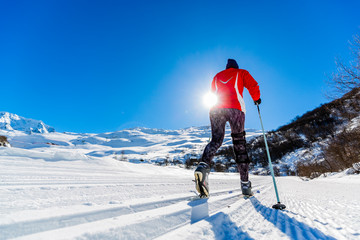 Woman cross country skie on a sunny winter morning in French Alps, 3 Valleys.