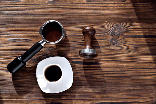 white coffee cup with saucer barista accessories for making coffee temper and coffee horn, morning side light wooden natural background close-up