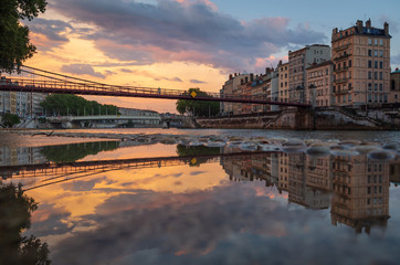 Sunset at an old footbridge over the Saone river in the old town of Lyon, France.