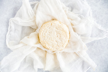 Round Soft Cow Cheese on Muslin Cloth and Blue Background