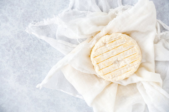 Small Round Soft Cow Cheese on Muslin Cloth and Blue Background