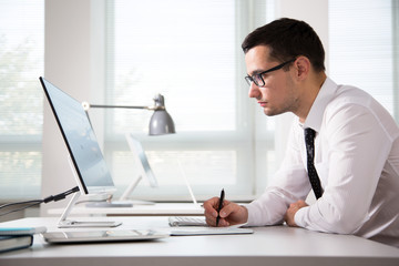 Serious businessman working with computer