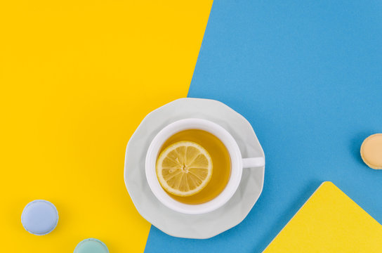 Lemon tea cup with macaroons on yellow and blue dual backdrop