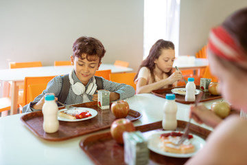 Schoolchildren having yummy lunch in canteen together