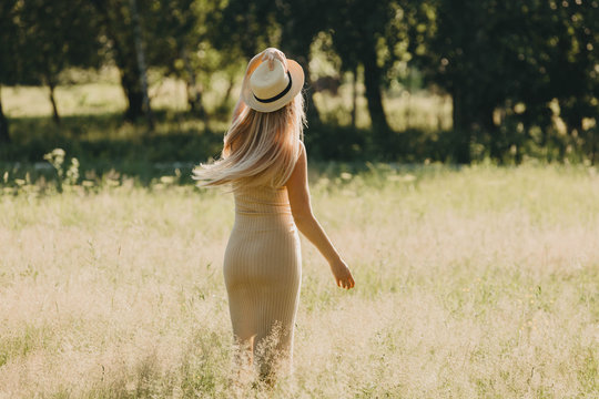 Woman with a hat in the summer park.