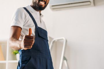 partial view of smiling african american repairman showing thumb up at camera
