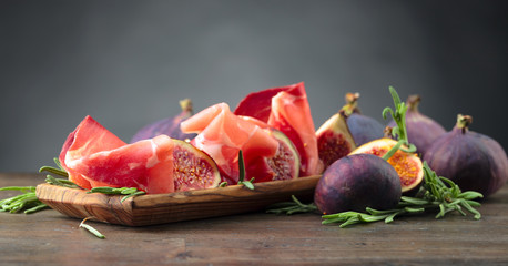 Fototapete - Prosciutto with figs and rosemary.
