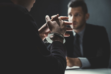 Criminal man with handcuffs being interviewed in interrogation room - fototapety na wymiar