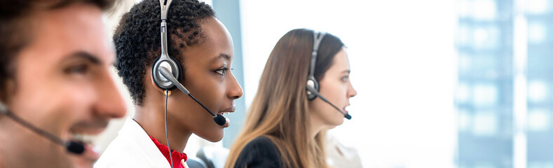 Group of diverse telemarketing team in call center office banner background