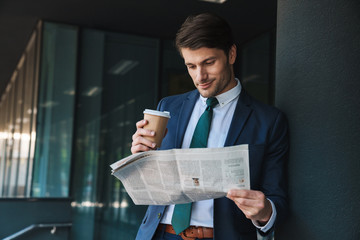 Photo of successful businessman reading newspaper and drinking coffee while standing outside job center