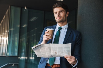 Photo of concentrated businessman reading newspaper and drinking coffee while standing outside job center