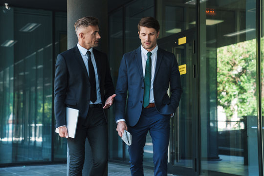 Portrait of two concentrated businessmen partners having conversation outside job center during working meeting