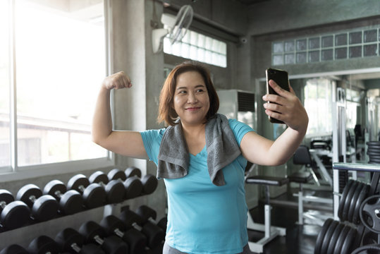 Senior asian woman attractive smiling active fitness in gym and taking a selfie showing muscle.