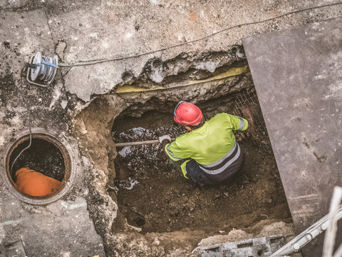 Unrecognizable workers repairing the sewage system in the street
