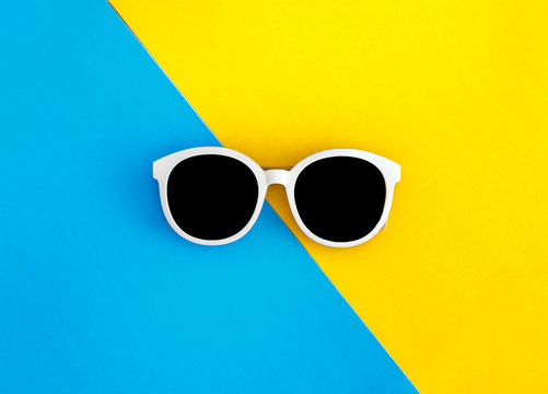 Sunny stylish white sunglasses on a bright blue-cyan and yellow-orange background, top view, isolated. Copy space. Flat lay
