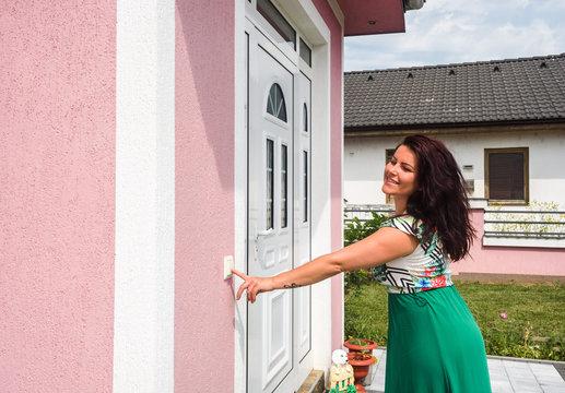 happy young woman ringing on doorbell on pvc front door