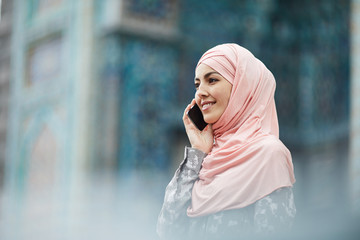 Positive pensive young Muslim woman in pink hijab standing outdoors and talking on mobile phone