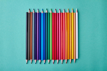 Row of multicolored pencils on color background. Set of colorful pencils on turquoise background....