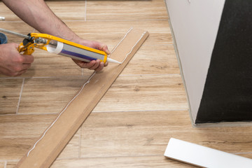 Mans hands installing white skirting board with caulking gun silicone from cartridge Wall mural