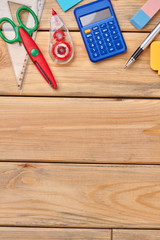 Office supplies on wooden background. Calculator, ballpoint pen, scissors, adhesive tape, erasers. Top view with copy space.