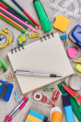 Notebook, pen and office supplies. Blank notepad, pen and various school accessories on wooden...