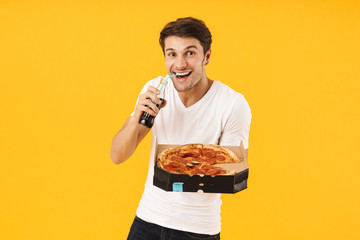Cheerful happy young man in casual white t-shirt eat pizza drinking soda isolated over yellow background.