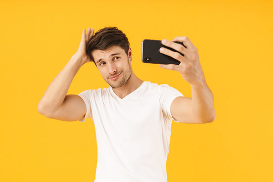 Man in casual white t-shirt take a selfie by mobile phone isolated over yellow background.