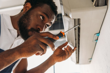 serious african american repairman fixing air conditioner with screwdriver