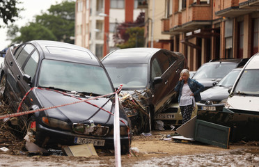 A woman speaks on the phone next to damaged cars after heavy rainfall in Tafalla