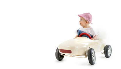 happy little girl in toy car isolated on white