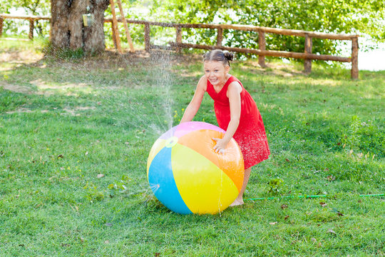 Kids play with water on hot summer day. Funny little girl playing with a water ball in the Sunny garden . Preschooler kid having fun with water spray. Summer outdoor recreation for children