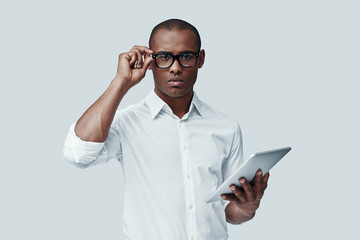 Ready to work. Handsome young African man using digital tablet and looking at camera while standing against grey background