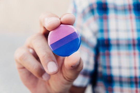 man with a bisexual pride flag badge.