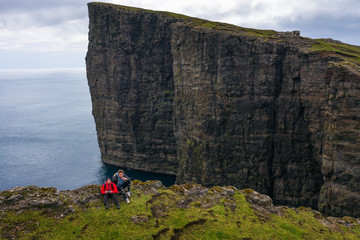 Wall Mural - Two hikers sitting on the edge of a cliff on Faroe Islands