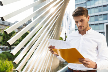 Concentrated handsome young business man standing near business center holding clipboard with...