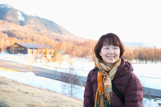 An older lady smiling while looking at the Winter scenery
