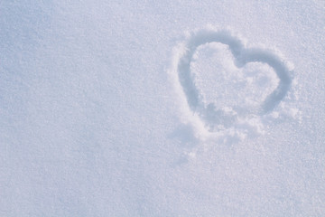 Heart drawn with a finger in the snow. Close-up. Background. Texture.