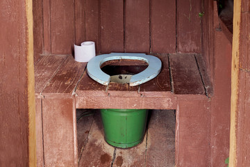 Interior of a country wooden outdoor toilet with a metal bucket as a waste tank and a roll of a paper