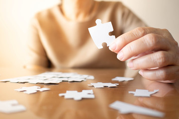 Wall Mural - Elderly female hands trying to connect pieces of white jigsaw puzzle on wooden table. Creative idea for Alzheimer's disease, dementia, memory loss and mental health concept. Close up. Copy space.