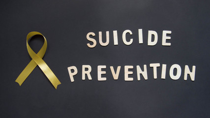 World suicide prevention day, 10th September. Yellow ribbon awareness and SUICIDE PREVENTION wooden word on black background. Mental health care concept.